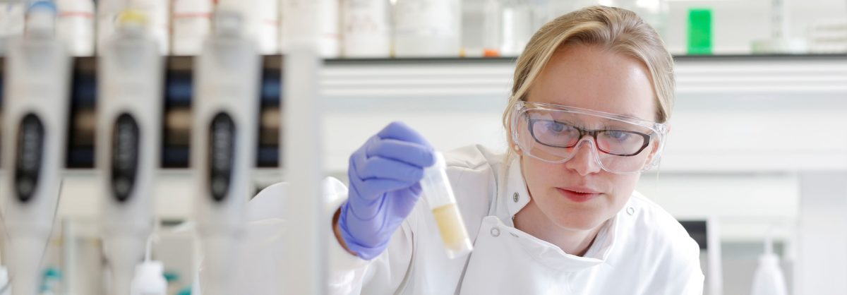 researcher looks at test tube