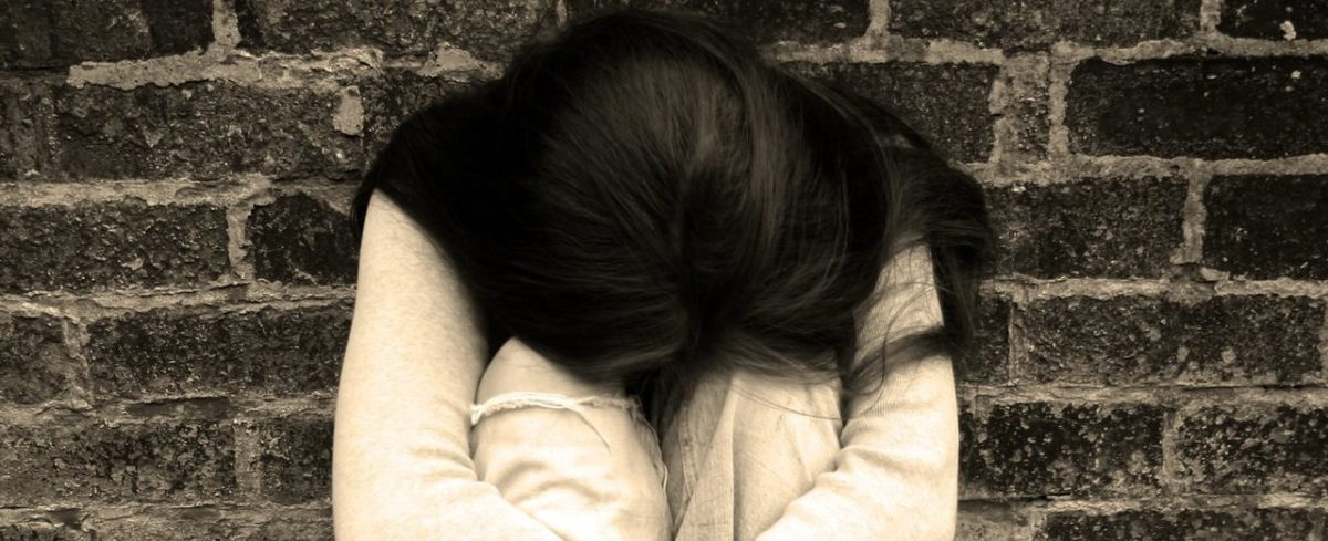 upset young woman hugging her knees, hiding her face