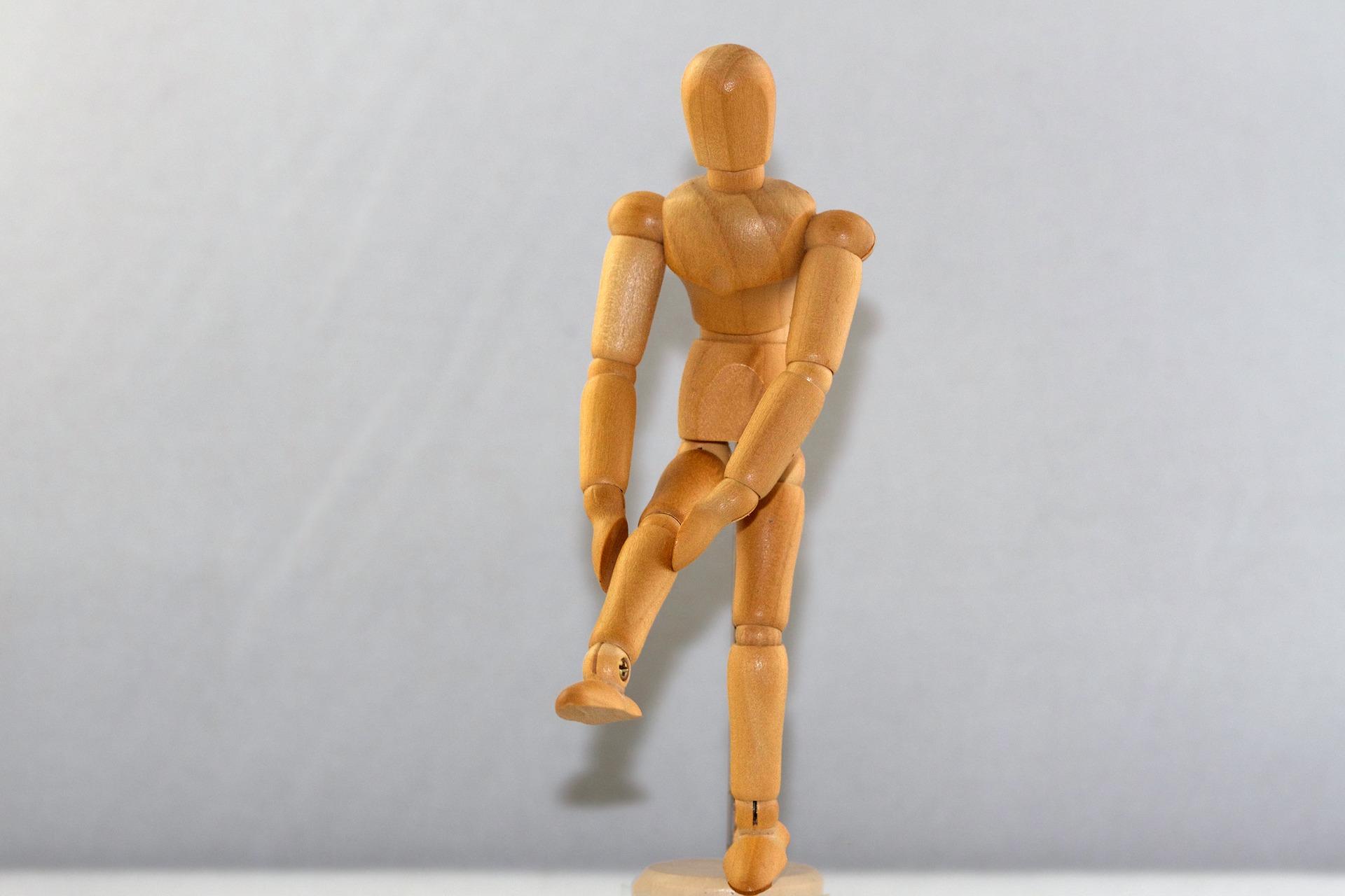 wooden figurine clutching knee