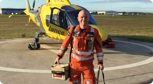 critical care paramedic in front of air ambulance helicopter