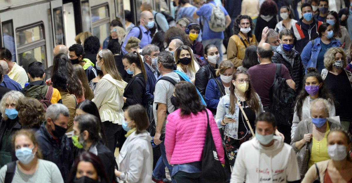 Subway train passengers with protective masks crowding to get on and off subway station platform on Serdika Metro station.