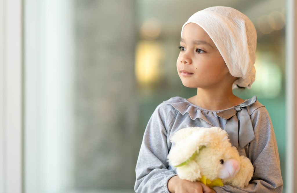 A beautiful little girl with cancer takes a break from treatment. She is standing near a large bay of windows in the hospital's corridor. The girl is wearing a headscarf and is holding a stuffed rabbit toy. She is looking out the window with a peaceful expression.