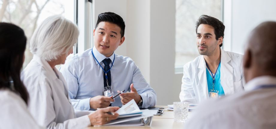 A group of doctors and healthcare professionals gather around a table for a discussion